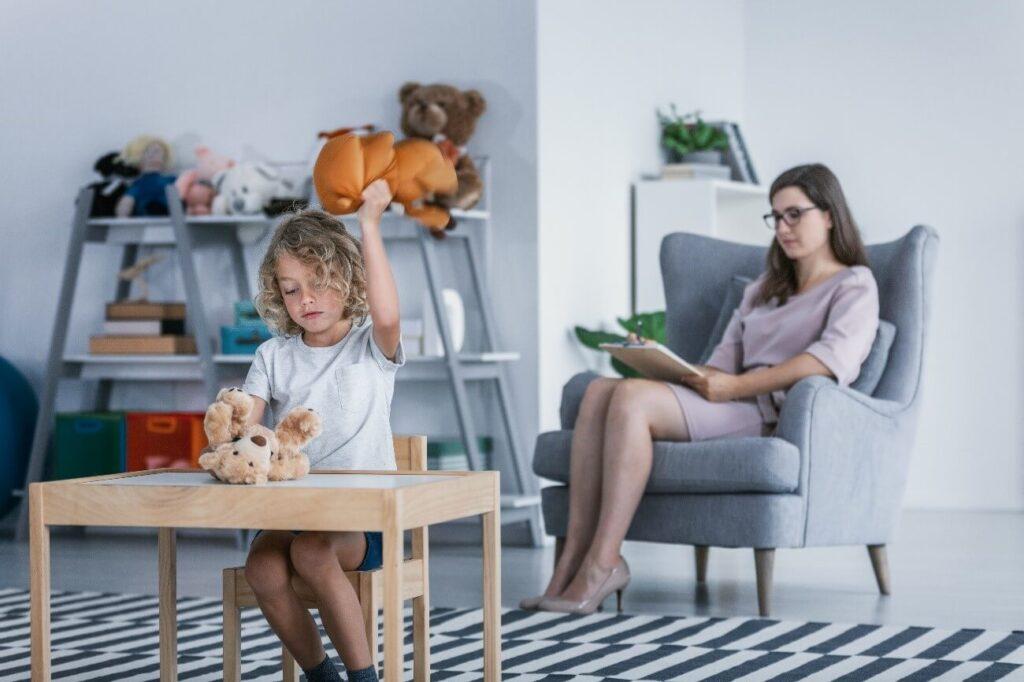 menina brincando em sessão de terapia com supervisão da psicóloga