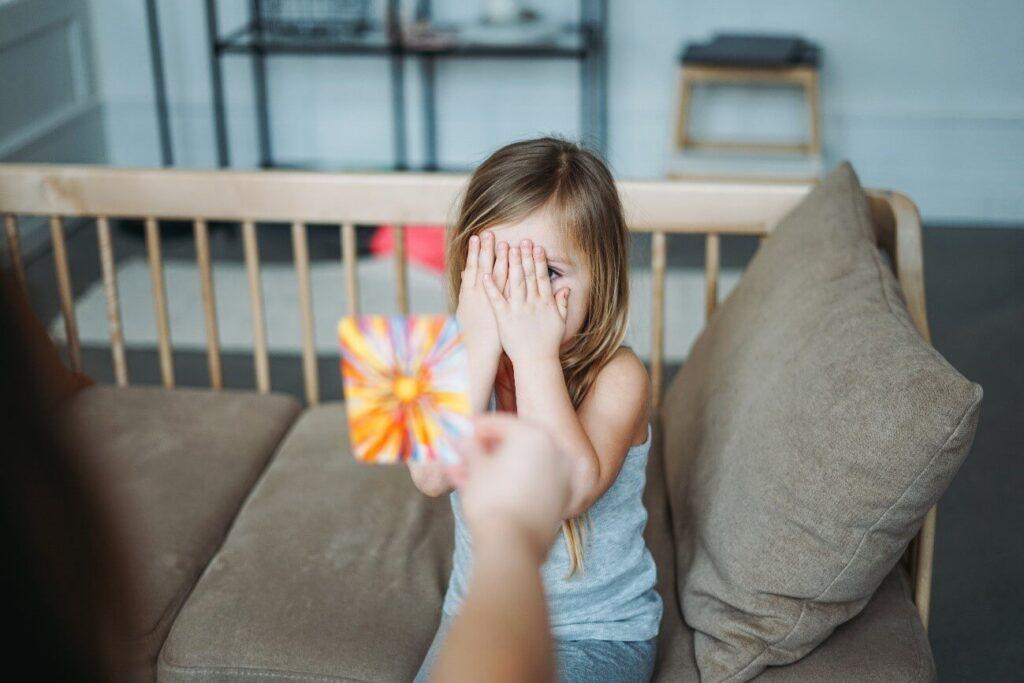 psicologia comportamental infantil - menina tampando o rosto com as mãos